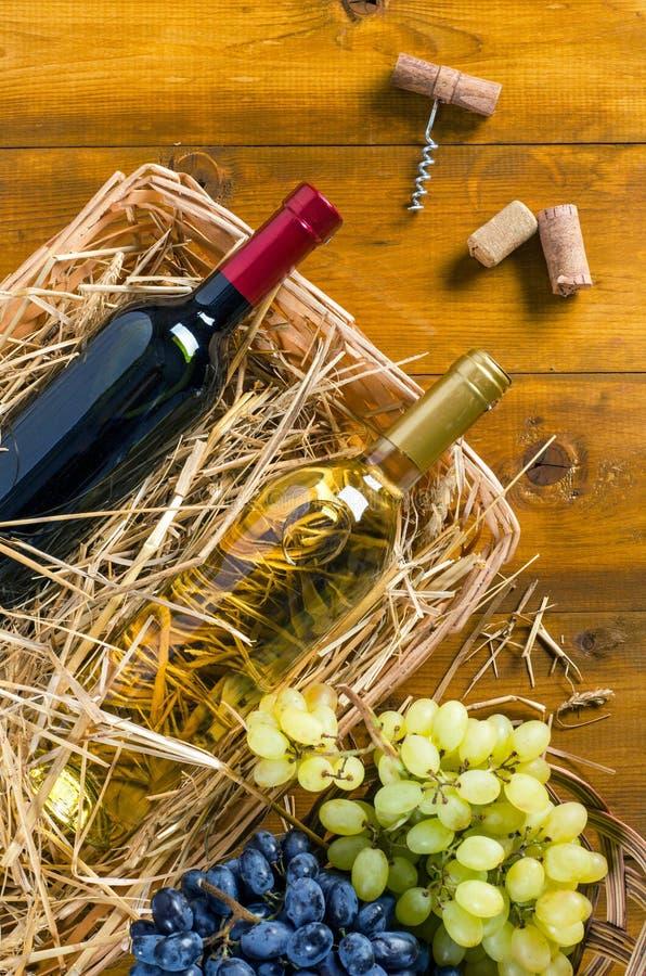 Två flaskor med vin, druvor, korkskruv, kork på träbackgr royaltyfri bild