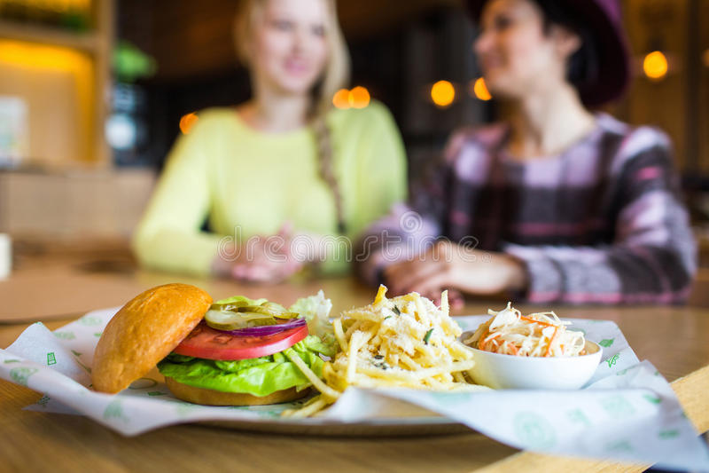 Två flicka - äta hamburgaren och dricka i en snabbmatmatställe; fokus på målet arkivfoto
