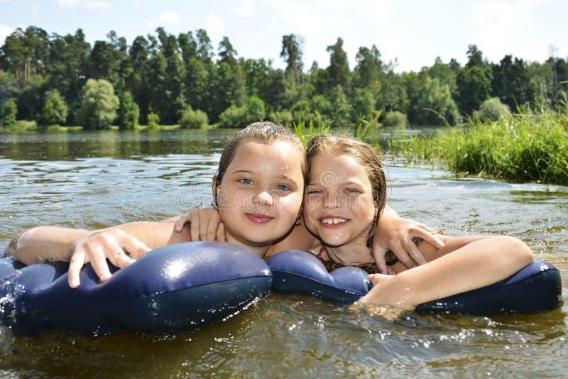 Två flickaflickvänner på sommarsjösimning i sjön och smen royaltyfri bild