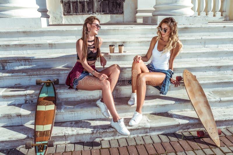 Två flickaflickvänner som sitter på trappan i sommar i staden, det talande samtalet, det lyckliga skrattet och leendet, skateboar royaltyfri foto
