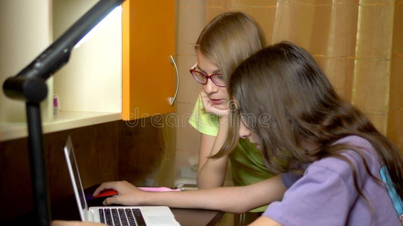 Två flickaflickvänner, tonåringstudenter sitter tillsammans på den utbildande tabellen och använder en bärbar dator i aftonen De  royaltyfria bilder