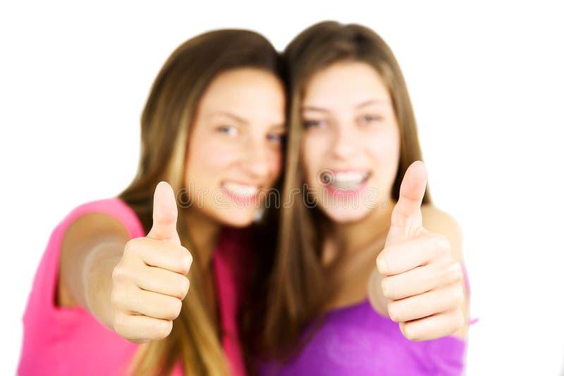Två flickatummar upp i den isolerade fokusen royaltyfri foto