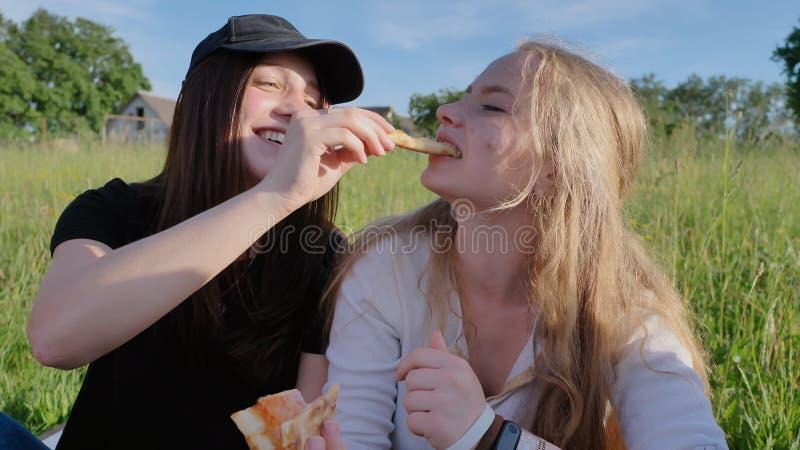 Två flickavänner av skolbarn äter pizza utomhus under solnedgången i aftonen fotografering för bildbyråer