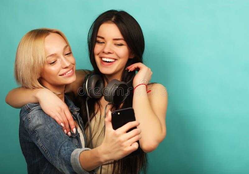 Två flickavänner i hipsterdräkt gör selfie på en telefon royaltyfria bilder