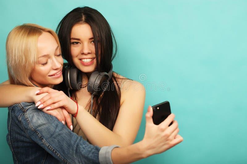 Två flickavänner i hipsterdräkt gör selfie på en telefon royaltyfri fotografi