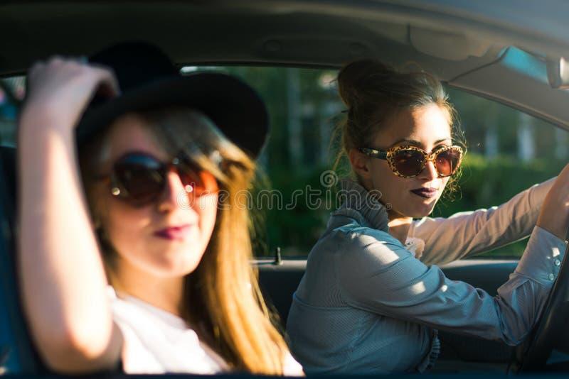 Två flickavänner på en vägtur med bilen royaltyfria foton