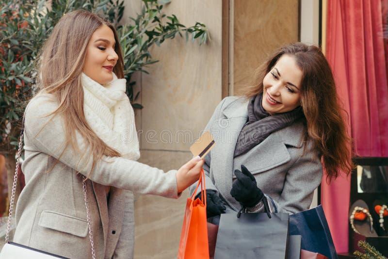 Två flickor är lyckliga med en kreditkort vid shoppingen arkivfoton