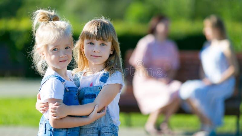Två flickor blev vänner och omfamnade, medan deras mödrar talar royaltyfria foton