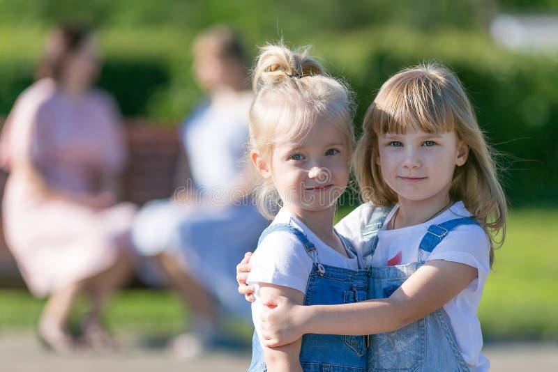Två flickor blev vänner och omfamnade, medan deras mödrar talar arkivbilder