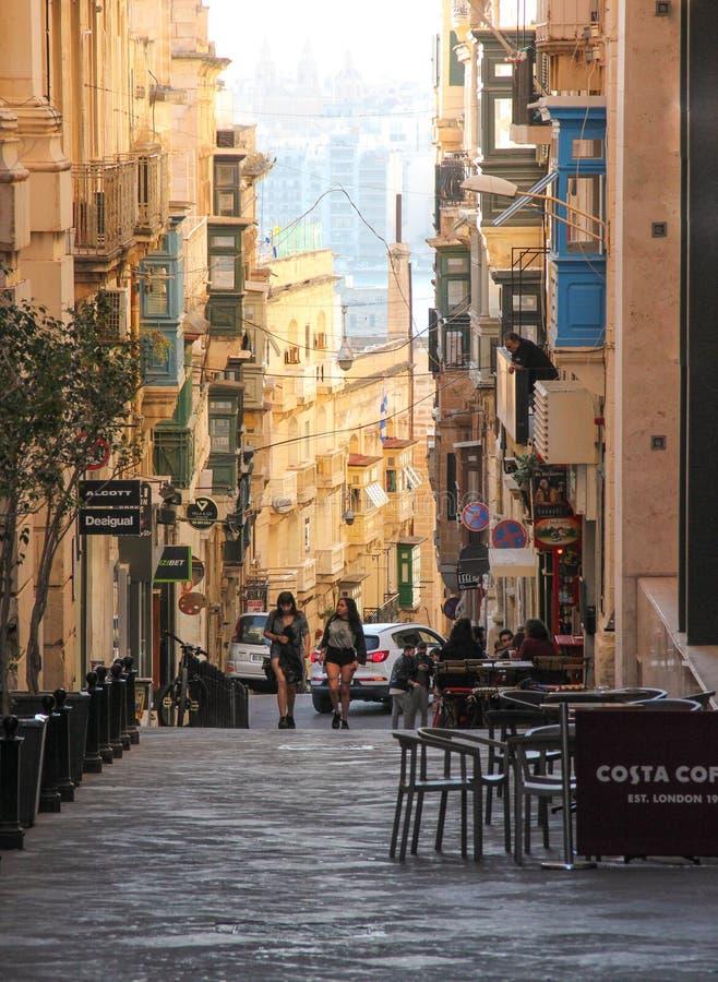 Två flickor går på den raka gatan av Valletta mellan kaféstolar arkivfoton