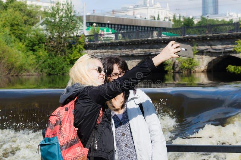 Två flickor gör en selphi nära en flod arkivfoton