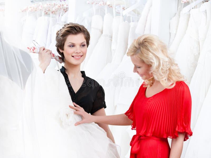 Två flickor har en god look på bröllopsklänningen royaltyfria foton