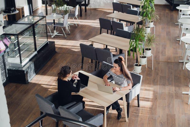 Två flickor i en coffee shop och att le och att skvallra som dricker kaffe royaltyfri bild