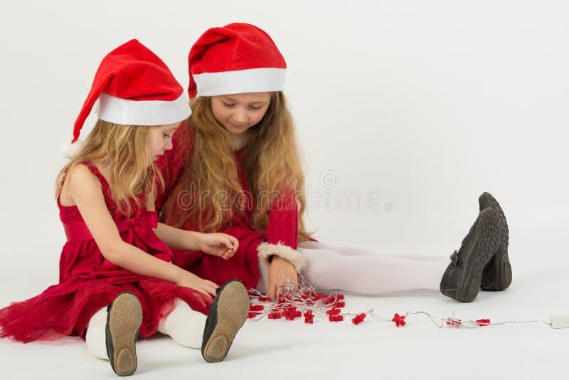 Två flickor i en röd klänning i lockSanta Claus sammanträde på golvet arkivfoton