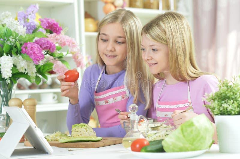Två flickor i förkläden som förbereder ny sallad royaltyfria bilder