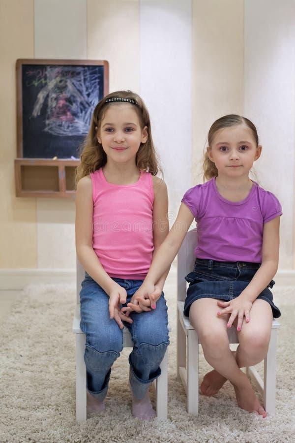 Två flickor i gameroomen sitter på stolar royaltyfri bild