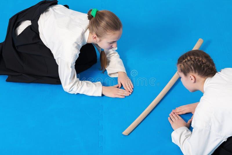Två flickor i hakamapilbåge på Aikidoutbildning fotografering för bildbyråer