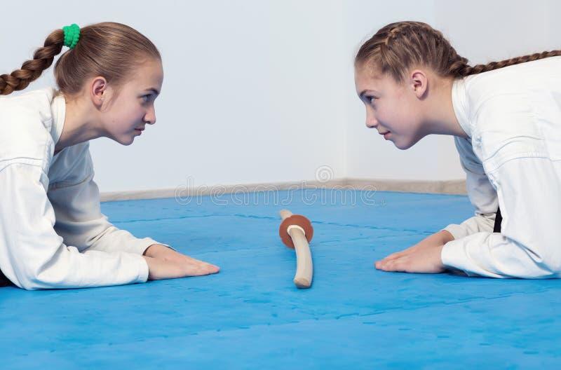 Två flickor i hakamapilbåge på Aikidoutbildning royaltyfri foto