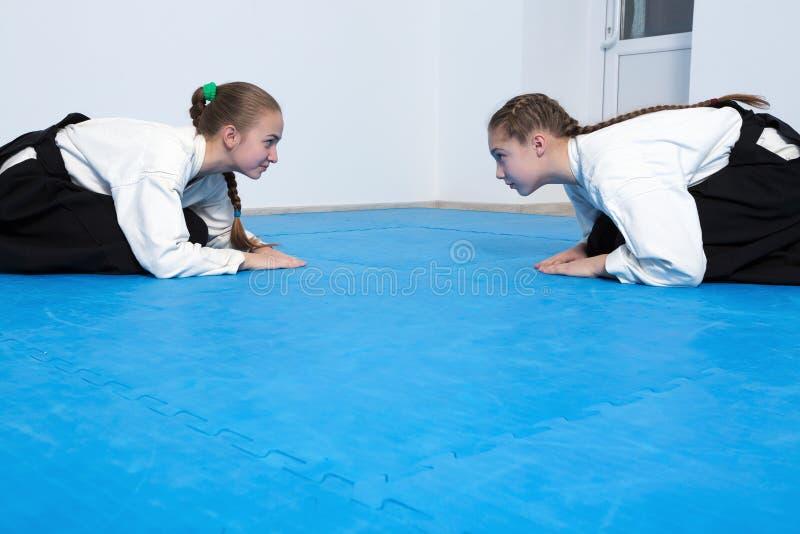 Två flickor i hakamapilbåge på Aikidoutbildning royaltyfria foton