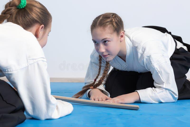 Två flickor i hakamapilbåge på Aikidoutbildning arkivbild