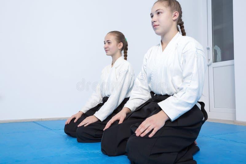 Två flickor i hakamasammanträde på Aikidoutbildning arkivbilder