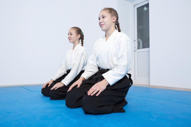 Två flickor i hakamasammanträde på Aikidoutbildning arkivfoto
