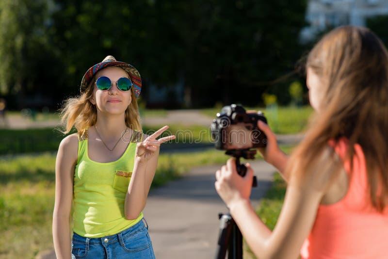 Två flickor i ljusa T-tröja Sommar i natur Lycklig le solglasögon i en hatt Antecknar en video i stad mot som kroken för hang för arkivbilder