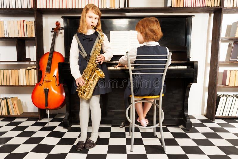Två flickor i skolaklänningar som spelar på instrument arkivbilder
