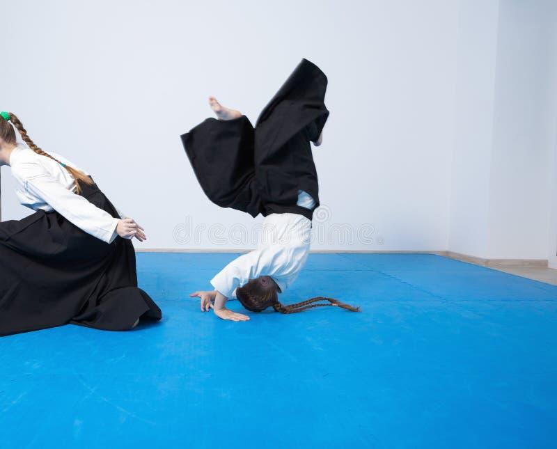 Två flickor i svart hakama övar Aikido på kampsportutbildning royaltyfria bilder