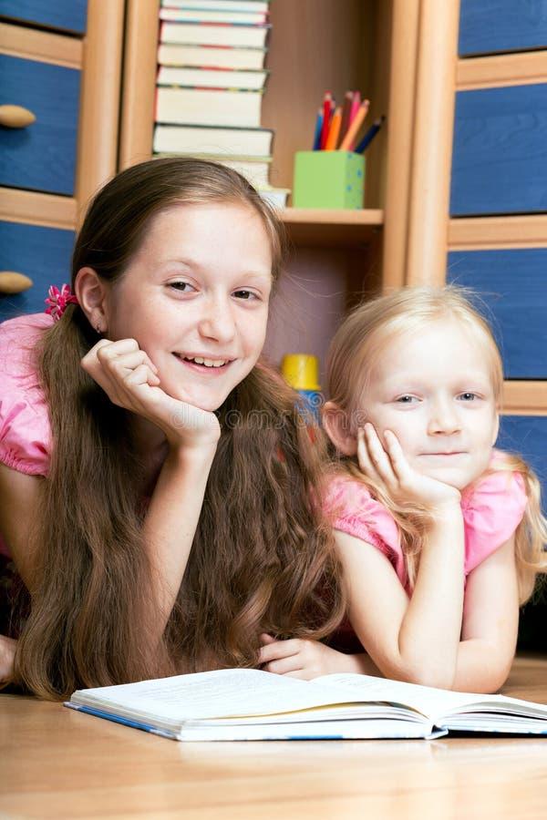 Två flickor läser boken arkivbilder