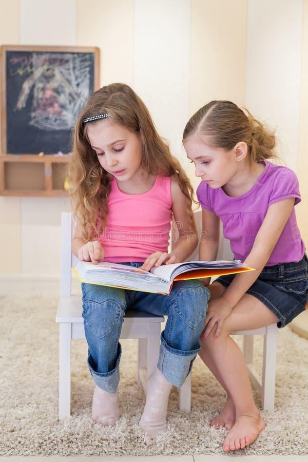 Två flickor läste en bok royaltyfria foton