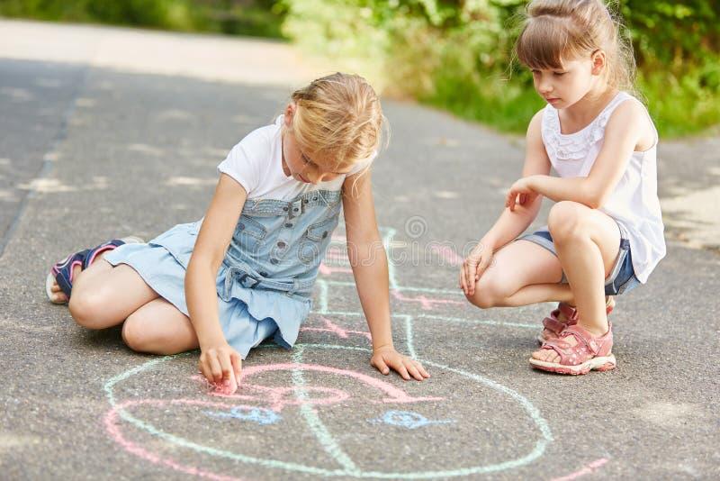 Två flickor målar leken med krita på golvet royaltyfri fotografi