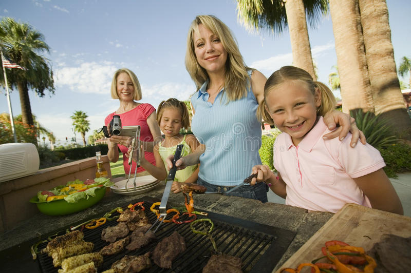 Två flickor (7-9) med familjen på den utomhus- grillfestståenden. arkivfoto