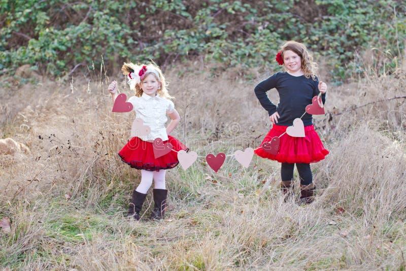 Två flickor med hjärtor arkivbild