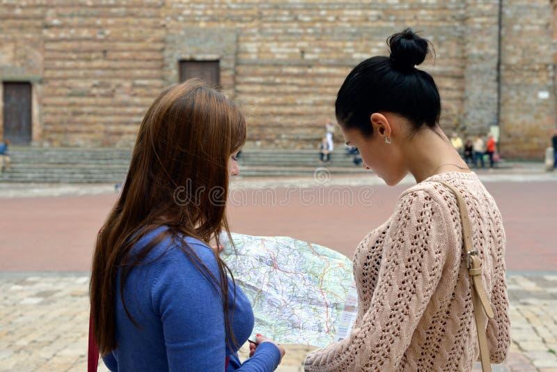 Två flickor med kartlägger royaltyfri fotografi