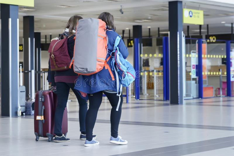Två flickor med stort bagage går till kollektivtrafikstationen: royaltyfria foton