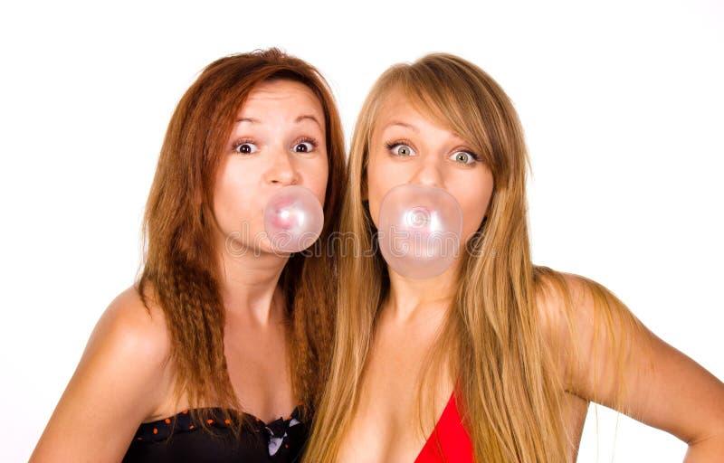Två flickor med tuggummi bubblor royaltyfria foton