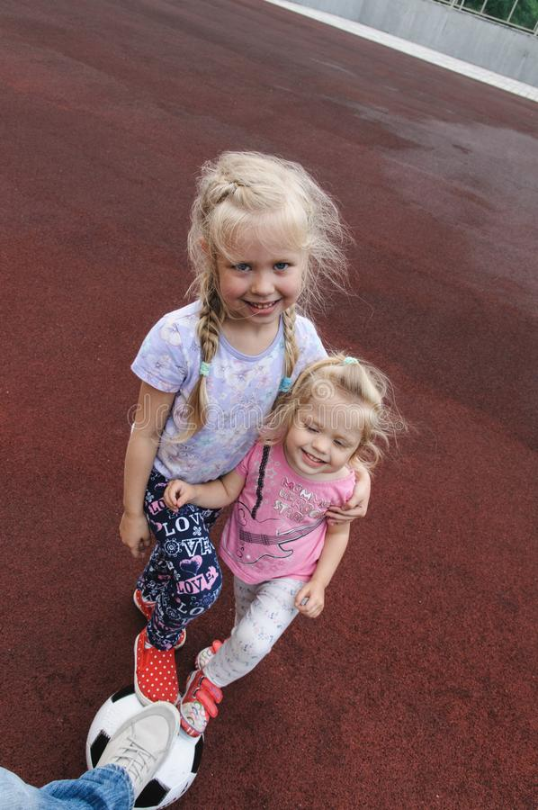 Två flickor och en fotbollboll arkivfoton