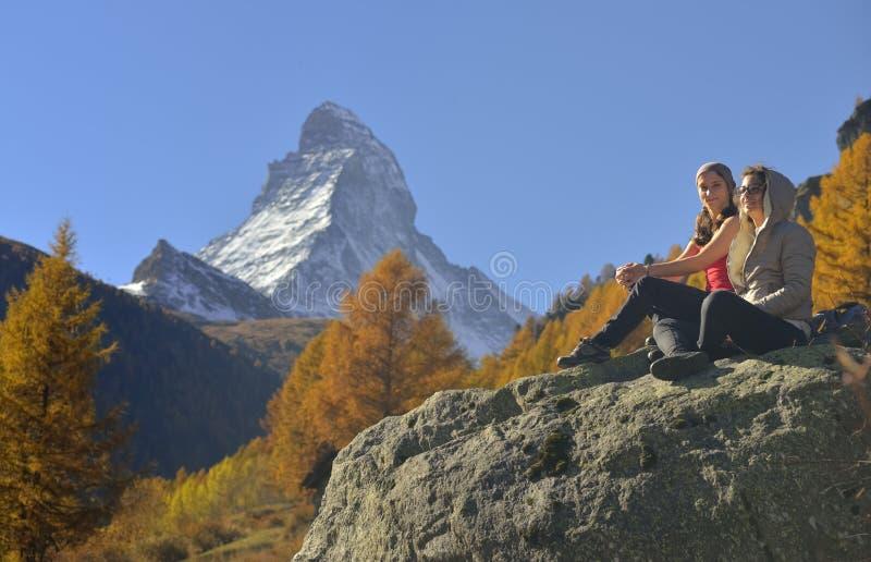 Två flickor och höstplats i Zermatt med det Matterhorn berget royaltyfri bild