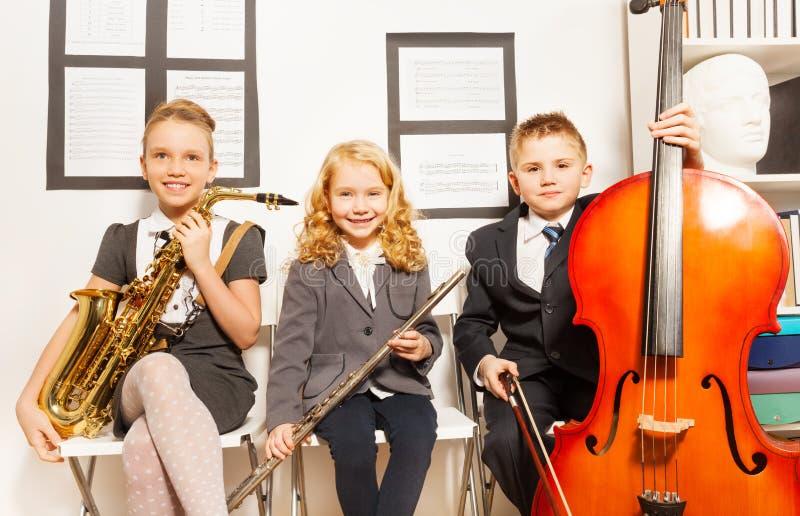 Två flickor och pojke som spelar musikinstrument royaltyfri bild