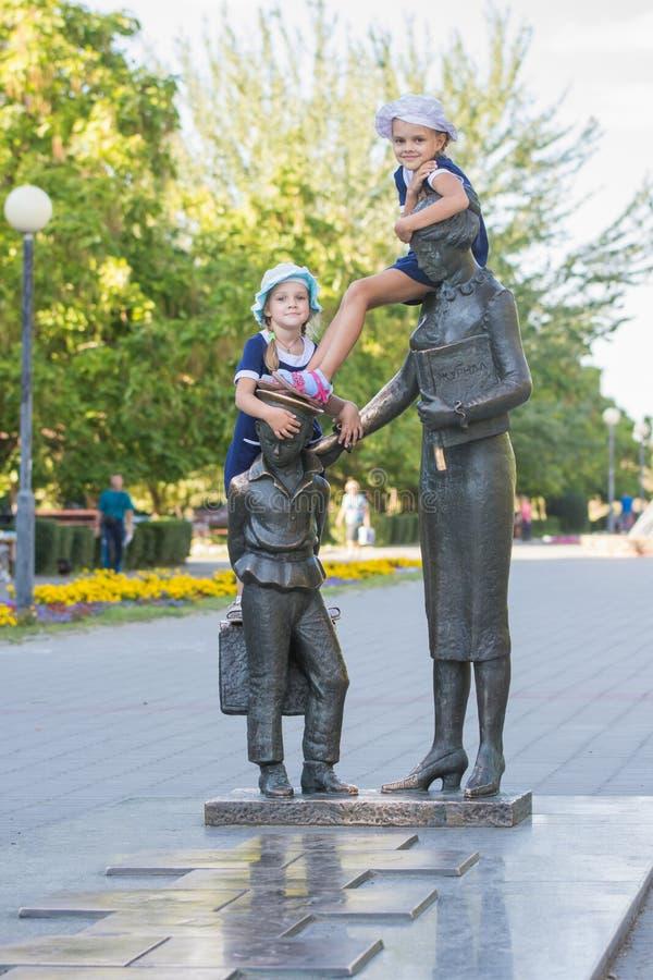Två flickor på monumentet till den första läraren royaltyfri foto