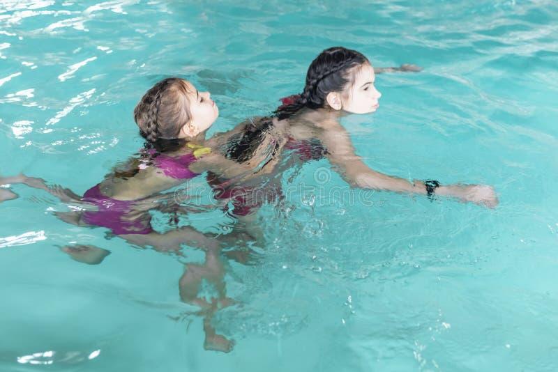 Två flickor simmar i pölen Två systrar i pölen Två lyckliga flickor spelar i pölen Härliga flickor simmar och ha gyckel i vatten arkivfoton