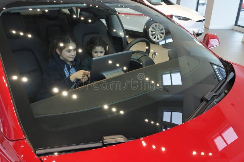 Två flickor sitter inom Tesla bilmodell 3 royaltyfria foton