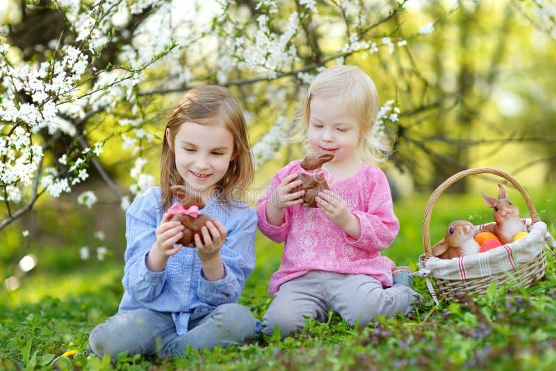 Två flickor som äter chokladkaniner på påsk royaltyfria bilder