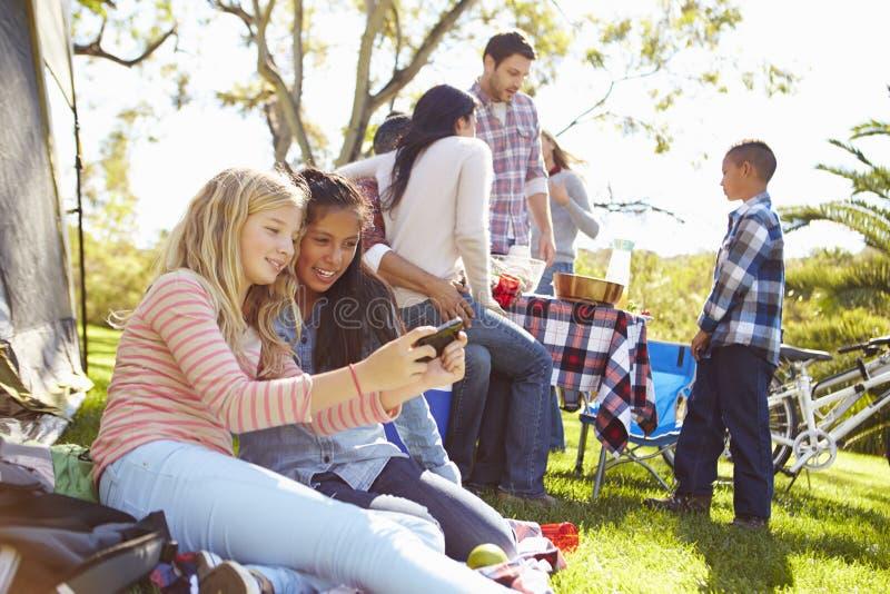 Två flickor som använder mobiltelefonen på campa ferie för familj arkivfoton