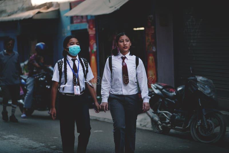 Två flickor som bär den enhetliga övergående Thamel gatan, går till skolan royaltyfria foton