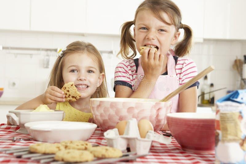 Två flickor som bakar i kök arkivbilder