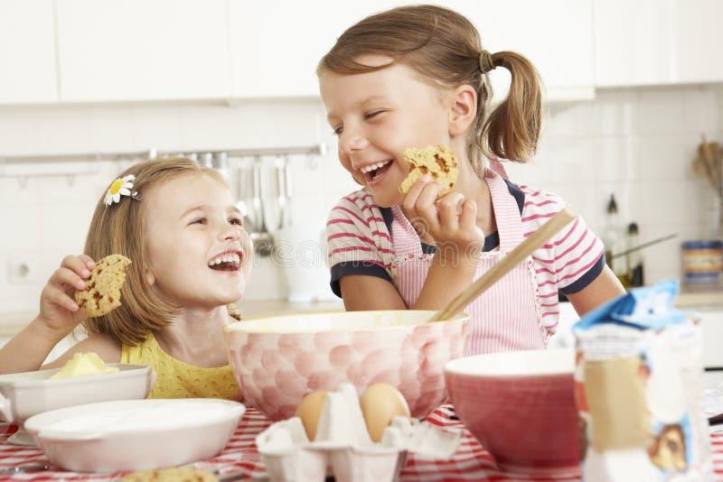 Två flickor som bakar i kök royaltyfri fotografi