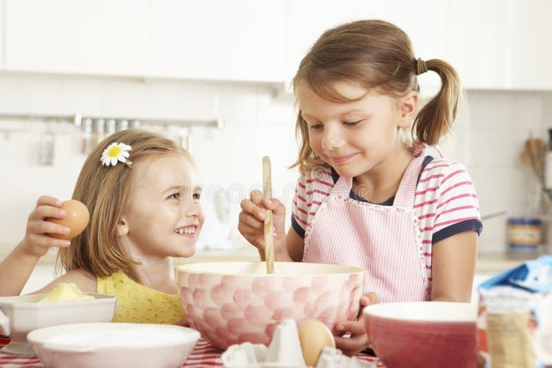 Två flickor som bakar i kök royaltyfri foto