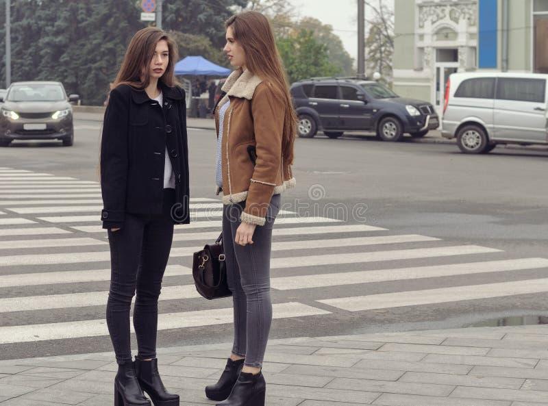 Två flickor som försöker att korsa vägen på en övergångsställe arkivbild